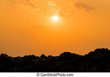 sunset over the silhouette mountain hills