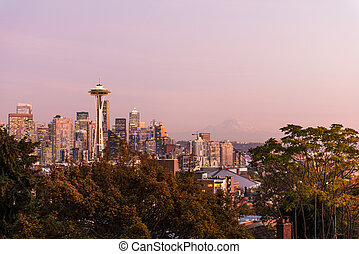 Sunset over the skyline of the city of Seattle and the profile of Mount Rainier in the background.