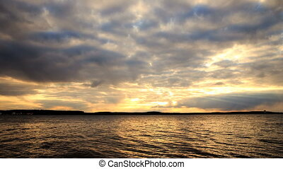 Sunset over the water by the lakeshore with dramatic cloudy sky