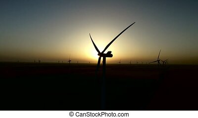 Sunset over the wind turbines on a wind farm in the quiet summer night. Silhouette. Aerial survey
