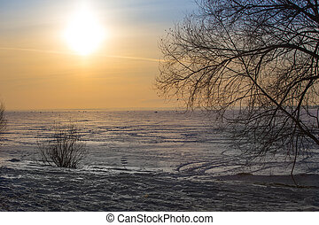 sunset over the winter ice surface of the lake