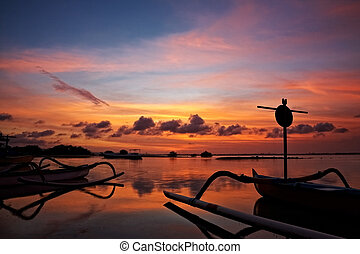 sunset over traditional fishing boats on Bali, Indonesia