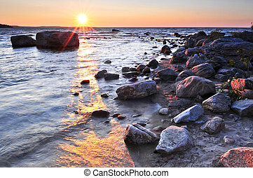 Sunset over water - Sunset at the rocky shore of Georgian ...