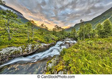 Sunset over wild river through birch forest in Norway