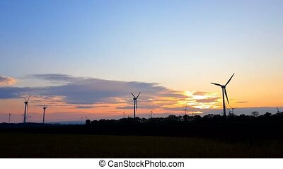 Sunset over wind turbines, Austria, ecology concept