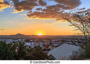 Sunset over Windhoek Central Business district with sun and mountains in the background, Windhoek, Namibia