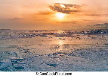 Sunset over winter frozen water lake