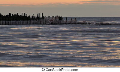 Sunset over winter sea with ice covered wooden pier