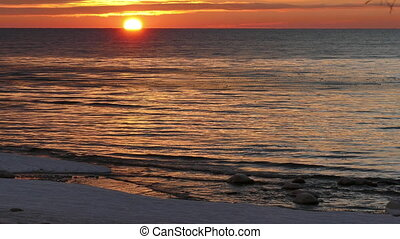Sunset over winter sea with some ice at shore