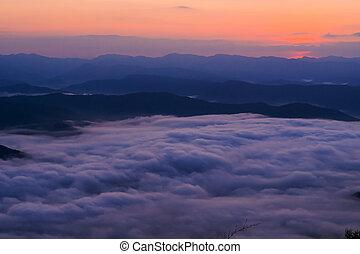 sunset overlooking mountains with Mist .