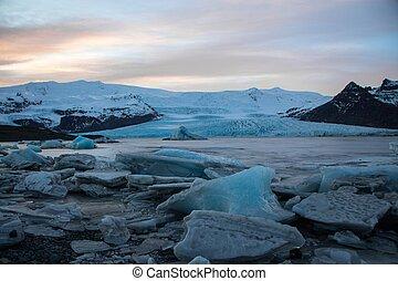 Sunset panorama of icebergs in Fjallsarlon lake lagoon of Vatnajokull glacier Fjallsjokull snow ice winter South Iceland