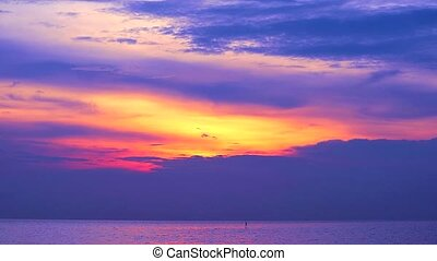 sunset purple on red cloud moving down on the sea and orange sky background