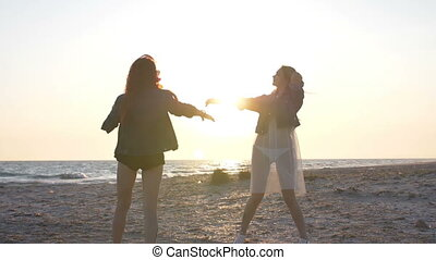 sunset rays over the sea illuminate the dance on the beach of two young sexy women dressed in boho style