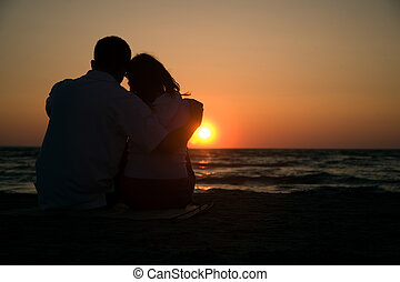 silhouetted couple watching a sunset