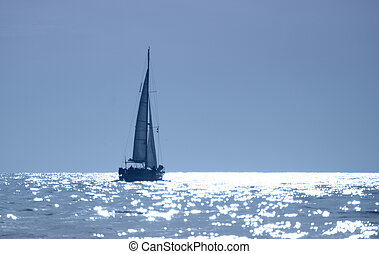 Sunset Sailboat - A sailboat cruises in the sparkling waters...