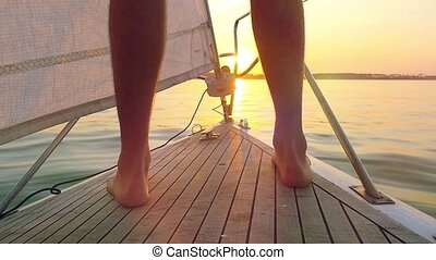 sunset sailing man on nose of yacht in ocean in slowmotion with flare and sunlight on calm reflected on the water