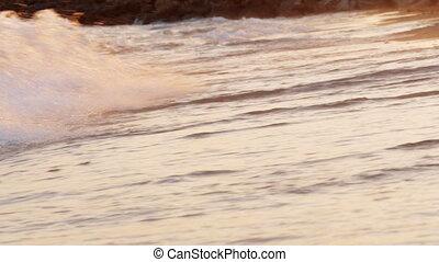 Sunset scene of foamy sea waves rolling in on the shore -...