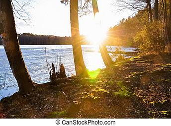 Sunset scene on the mossy shore of melting frozen lake. Early spring nature landscape