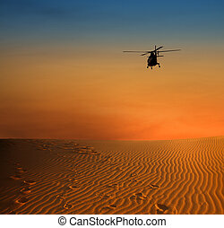 helicopter over dersert - sunset scene with silhouette of a ...