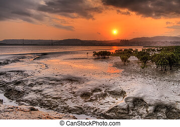 Sunset scenic with red sun and silver silt of river in dusk.