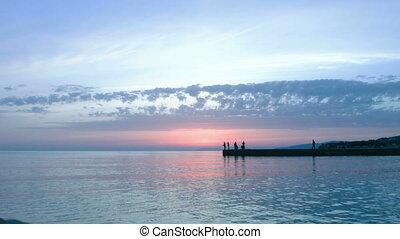 Sunset. Sea. People.
