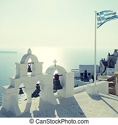 Greek flag and bell tower in Oia village, Santorini, Greece
