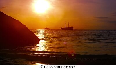 Sunset Seascape with Waves and Boats under a Red Sky