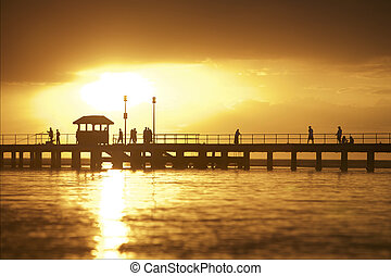 Sunset setting over pier