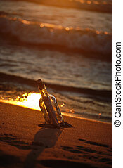 Sunset Shore - Message in a bottle on beach at sunset.