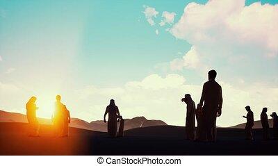 Sunset silhouette Arabic men with bird of prey on desert...