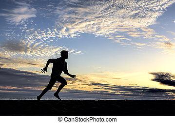 Sunset silhouette of boy running.