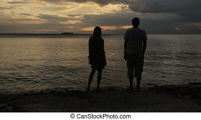 sunset silhouette of couple on the beach