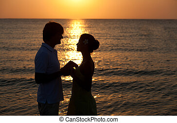 sunset silhouette of happy young lovers on the beach. honeymoon