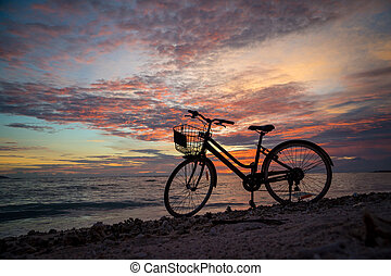 Sunset silhouette of vintage bicycle on the beach