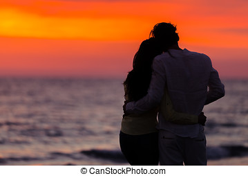 sunset silhouette of young couple in love hugging at beach