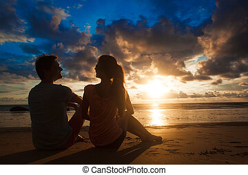 sunset silhouette of young couple in love sitting at beach