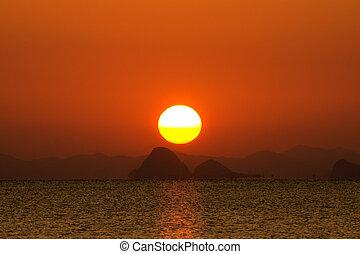 Sunset sky and big sun over the lake.