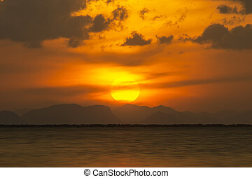 Sunset sky at the lake with clouds and silhouette mountain.