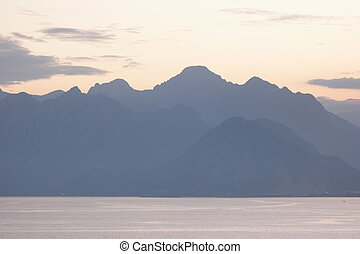 Sunset sky background with mountain range silhouette.