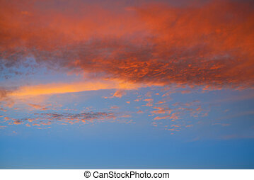 Sunset sky with orange clouds and blue