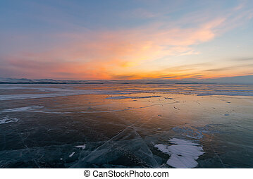 Sunset skyline over frozen water lake in winter season