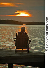 sunset solitude - elderly person sitting alone in chair...