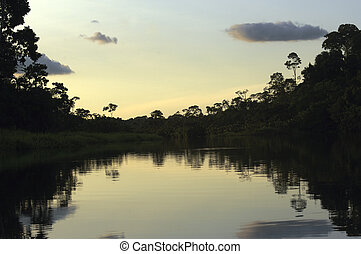 Sunset / Sunrise at the Amazon - Red sky over the water with...