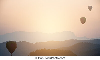 Sunset - sunrise background with hot air balloons and layer of mountain.