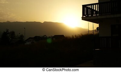 sunset, sunrise in the mountains. silhouette of a house in the mountains against the background of dawn 4k