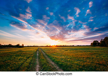 Sunset, Sunrise Over Rural Field Meadow. Bright Dramatic Sky