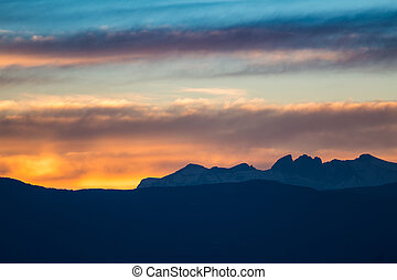 Sunset / sunrise with vivid colorful sky, clouds and mountains dark silhouettes.