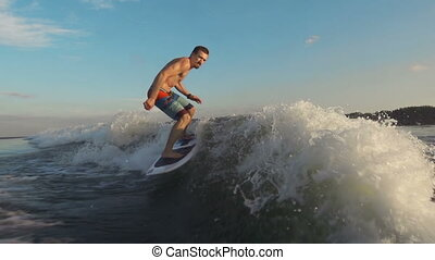 Sunset Surfing - Slow motion of surfer gliding along waves...