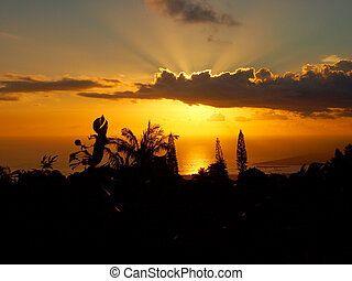 Sunset through the clouds over the ocean seen from Tantalus mountain past tropical silhouette of trees