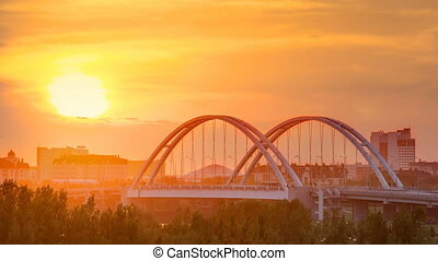 Sunset timelapse above the Bridge with the transport and clouds on the background. Central Asia, Kazakhstan, Astana